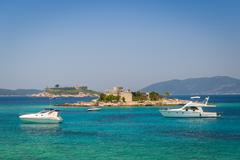 Luxury motor yachts at anchor near the old fortress on a small island Stock Photos