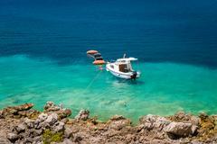 Small fishing boat moored at paradise bay shore - stock photo