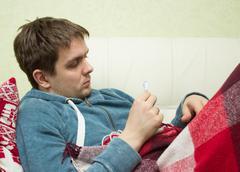 Ill man checking temperature, lying on sofa Stock Photos