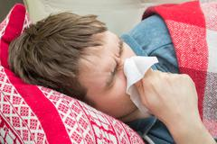 Man with cold lying and sneezing in tissue - stock photo