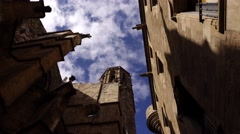 Gothic Church bell tower and walls against blue sky, low angle dolly shot Stock Footage