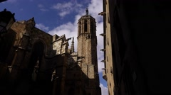 Gothic Cathedral bell tower dolly shot, look up from narrow lane Stock Footage