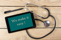 We make it easy - Workplace of a doctor. Tablet, medical stethoscope, black pen - stock photo