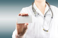 Female doctor's hand holding blank business card. Close up shot - stock photo