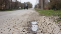 The tractor  on the road  holes on the asphalt road  Stock Footage