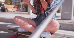 Teen skater girl eating ice cream at the seaside - stock footage