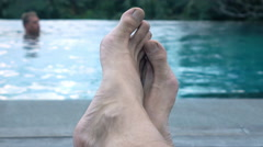 Male legs on daybed by the swimming pool, man swimming in background Stock Footage