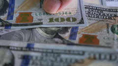 Male hand picking up one hundred dollar bills - stock footage