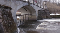 Water flowing underneath the old bridge. Melting ice, foam, antic stonework. - stock footage