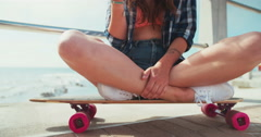 Skater girl sitting on a skateboard holding a phone Stock Footage