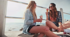 Teen hipster friends enjoying ice cream at the beachfront Stock Footage