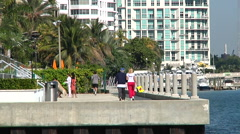 People jogging and walking on a Brickell walkway by the bay in Miami. Stock Footage
