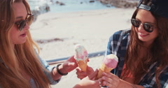 Urban teenage hipster girls eating ice cream on summer day Stock Footage