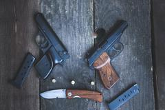 Weapons on the background of a wooden table - stock photo