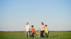 Happy young family with children  running, walking around the field Stock Footage