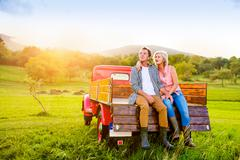 Senior couple sitting in back of red pickup truck Stock Photos