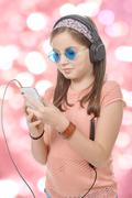 preteen girl listening to music with his smartphone, bokeh background - stock photo