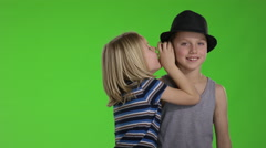 Brother whispers a joke to older brother in front of greenscreen Stock Footage