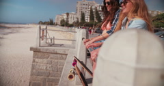 Skater girls on beach standing at a railing laughing Stock Footage