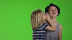 Child whispers a joke to another child in front of greenscreen Stock Footage