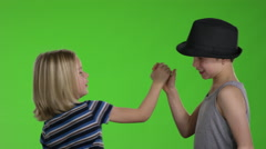 Two kids giving high five to each other in front of greenscreen Stock Footage