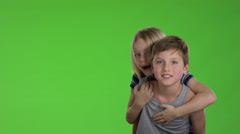 Older brother carries younger at his back while they are smiling to the camer Stock Footage