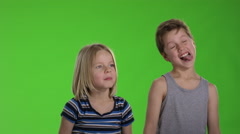 Two kids making faces in front of greenscreen Stock Footage