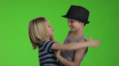 Two childs hugging each other and having fun in front of greenscreen Stock Footage