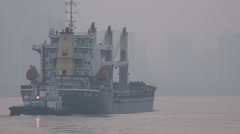 A large cargo vessel sails through central Shanghai, China Stock Footage