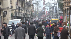 People walk through a busy street in an old part of Shanghai, China Stock Footage