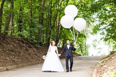 summer holidays, celebration and wedding concept - couple with colorful balloons - stock photo