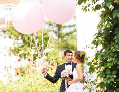 Summer holidays, celebration and wedding concept - couple with colorful balloons Stock Photos
