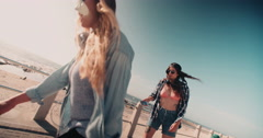 Teenaged girls riding skateboards along a walkway at the beach Stock Footage