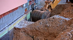 Digger making a hole near house wall long shot Stock Footage