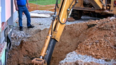 Digger dig inside a hole while worker overseeing Stock Footage