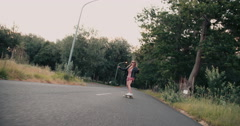 Skater girl in leather jacket riding along road with trees Stock Footage