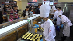 Chinese pastry chefs prepare egg tarts, food beverage trade show in Shanghai Stock Footage