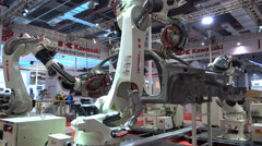 China industry, robot arms assemble car, manufacturing, factory, trade show - stock footage