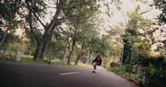 Teenage girl riding her longboard along a tree-lined road Stock Footage