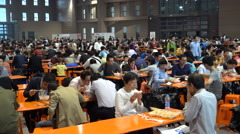 Busy crowded restaurant canteen at trade show, people eat lunch, Shanghai, China Stock Footage