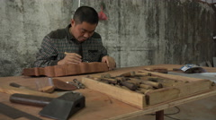 Chinese carpenter carving tropical hardwood in small furniture factory - stock footage