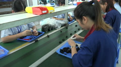 Female workers assemble audio parts in electronics factory Guangdong, China - stock footage