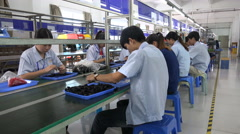 Chinese factory workers at assembly line, industrial center Shenzhen city - stock footage
