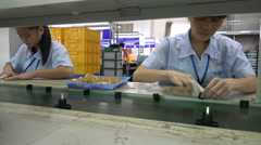 Employees of an electronics factory assemble components in Shenzhen, China Stock Footage