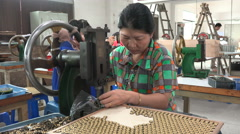 Woman assembles buttons for the garment industry in a factory in Dongguan, China Stock Footage