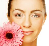 Stock Photo of Beautiful young woman with gerber flower