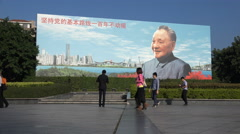 Pedestrians walk past billboard of Deng Xiaoping in Shenzhen, China Stock Footage