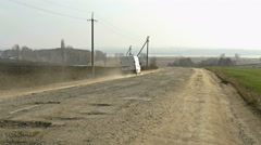 White van traveling at destroyed road in calm countryside. Springtime landscape. Stock Footage