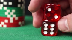 Red dice and casino chips in hand on green table Stock Footage