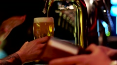 The barman pours beer into a glass for beer pub visitor Stock Footage
